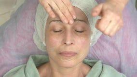 Cosmetician που εφαρμόζει την του προσώπου μάσκα πηκτωμάτων απόθεμα βίντεο