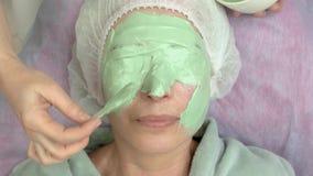 Cosmetician που εφαρμόζει τη μάσκα προσώπου άλατος αλγινικού οξέος φιλμ μικρού μήκους
