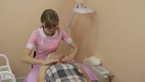Cosmetician που προετοιμάζεται να κάνει το του προσώπου μασάζ απόθεμα βίντεο