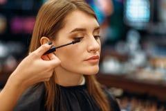 Cosmetician и женский клиент в магазине макияжа стоковые фото