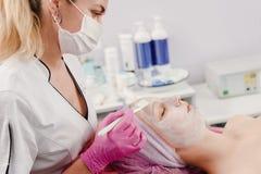 Cosmetician прикладывая сливк стоковая фотография rf