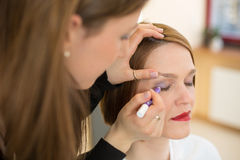 Cosmetician applying eye makeup. Cosmetician applying eye shadow to customer royalty free stock image