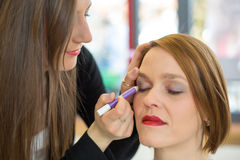 Cosmetician applying eye makeup Royalty Free Stock Photos