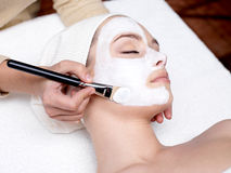 Cosmetician applying facial mask on female face Stock Image