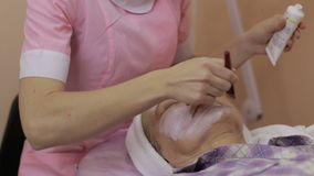 Cosmetician applying facial mask to female client stock video