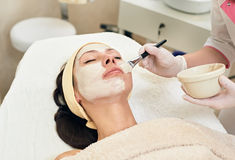 Cosmetician applying facial mask Stock Images