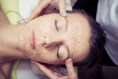 Cosmetician applying facial mask at young woman in spa salon. Beauty treatment concept. Woman relaxing in spa salon. Cosmetician applying facial mask at young royalty free stock photos