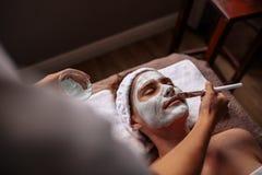 Cosmetician che applica mascherina facciale sul fronte femminile fotografie stock