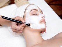 Cosmetician che applica mascherina facciale sul fronte femminile immagine stock