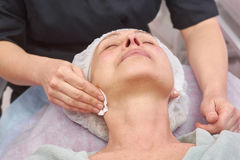 Cosmetician cleaning face, mature woman. Hand using cotton pad Stock Images