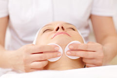Cosmetician cleaning face using cotton pads Royalty Free Stock Image