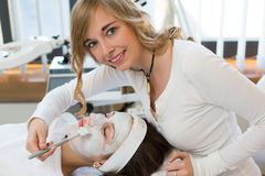 Cosmetician giving client facial skincare mask. Cosmetician applying facial skincare mask to customer stock photos