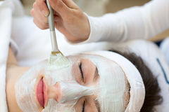 Cosmetician giving client facial skincare mask. Cosmetician applying facial skincare mask to customer royalty free stock images