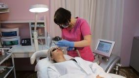 Cosmetician perfiming photo rejuvenation stock footage