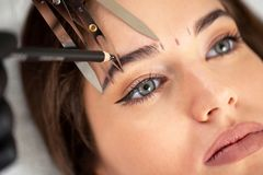 Cosmetician preparing to make a legit appearance of naturally full brows. On the face of a pretty young woman stock images