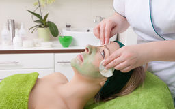 Cosmetician removing facial mask from woman face. Royalty Free Stock Photos