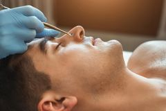 Cosmetician using blackhead remover. For cleaning man face in spa salon stock image