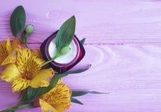 Cosmetico crema di salute, alstroemeria dell'ingrediente del fiore su un woodencleaner Fotografie Stock