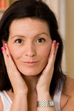 Cosmetics. Woman checks her skin in the mirror for blemishes Royalty Free Stock Photo