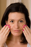 Cosmetics. Woman checks her skin in the mirror for blemishes Stock Photography