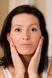 Cosmetics. Woman checks her skin in the mirror for blemishes Stock Image