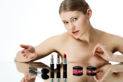 Cosmetics. Young woman presenting various cosmetic items Royalty Free Stock Photo