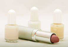 Cosmetics. A lipstick and three fingernail polish bottles composition stock image
