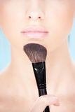 Cosmetics. Part of a woman's face and makeup brush stock photo