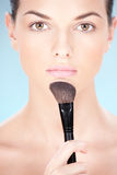 Cosmetics. Portrait of a pretty young woman holding powder brush royalty free stock photo