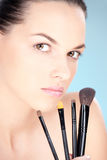 Cosmetics. Pretty woman holding set of make up brushes royalty free stock photos
