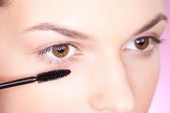 Cosmetics. Pretty woman applying mascara on eye Royalty Free Stock Image