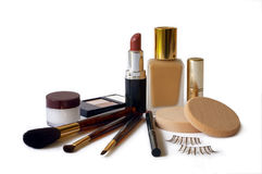 Cosmetics. Assortment of women's cosmetics -  foundation, lipstick, eyeshadow, lip liner, lip balm, applicator brushes & fake eyelashes Stock Photos