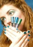 Cosmetics. Blonde woman holding colorful cosmetics Stock Photos