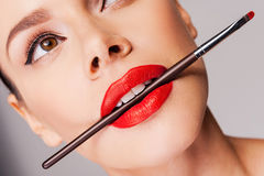 Cosmetics artistry. Close-up of a beautiful woman with red lips holding make-u[p brush in her mouth and looking away while standing against grey background stock image