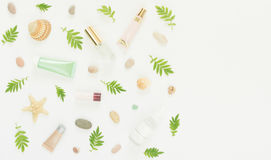 Cosmetics background. Cosmetics SPA makeup tubes, bottles, sea pebbles and shells on white background. Flat lay, top Stock Images