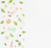 Cosmetics background. Cosmetics SPA makeup tubes, bottles, sea pebbles and shells on white background. Flat lay, top view. stock photos