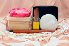 Cosmetics on the background of pink fabric. Lipstick, powder, powder puff and a pencil on a pink background Stock Photo