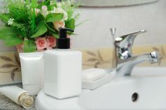 Dispenser cream bottle and soap on a wash basin stock photos