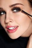 Cosmetics. Beautiful Woman With Perfect Makeup Applying Mascara Stock Image