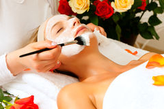 Cosmetics and Beauty - applying facial mask. Woman having a mask or cream applied in the course of a beauty or wellness treatment Royalty Free Stock Photography