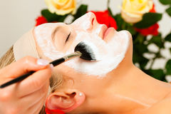 Cosmetics and Beauty - applying facial mask. Woman having a mask or cream applied in the course of a beauty or wellness treatment Stock Photos