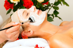 Cosmetics and Beauty - applying facial mask. Woman having a mask or cream applied in the course of a beauty or wellness treatment Stock Photography