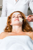 Cosmetics and Beauty - applying facial mask. Woman having a mask or cream applied in the course of a beauty or wellness treatment Stock Images