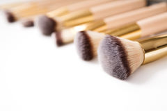 Cosmetics, beauty, make-up brushes set in row, shallow depth. Cosmetics and beauty. Make-up brushes set in row on white isolated background. Selective focus Stock Photography