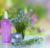 Cosmetics bottles with flowers Stock Photography