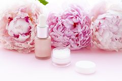 Cosmetics bottles on the pink background with flowers. Close up royalty free stock image