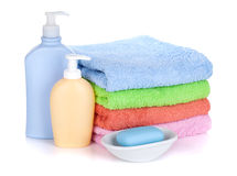 Cosmetics bottles, soap and colored towels Royalty Free Stock Image