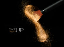 Cosmetics brush with glowing face powder. Dust explosion. Soft cosmetics brush releasing a cloud of glowing sparkling face powder over a black background with royalty free stock photography