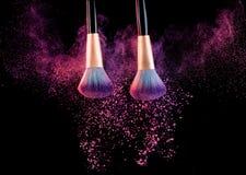 Cosmetics brush with powder explosion on black stock image