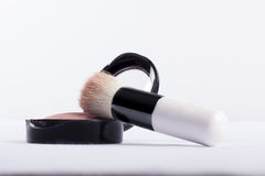 Cosmetics brush resting a blusher. Low angle view of a cosmetics brush resting a small compact of blusher to contour and enhamce the cheek over a white Royalty Free Stock Photo